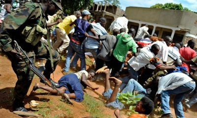 "A Ugandan military UPDF officer (L) disperse supporters of Ugandan opposition leader Kizza Besigye who had gathered in large numbers to welcome him back to Kampala from Nairobi on May 12, 2011 where he had gone to seek medical treatment for injuries sustained after he was attacked by state security personnel during an opposition demonstration. Ugandan President Yoweri Museveni vowed to stamp out ""disrupting schemes"" on May 12 as he was sworn in for a fourth term while masses of opposition supporters welcomed home his rival, Kizza Besigye. AFP PHOTO/Tony KARUMBA (Photo credit should read TONY KARUMBA/AFP/Getty Images)"